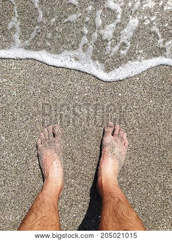 man feet and legs by the ocean.