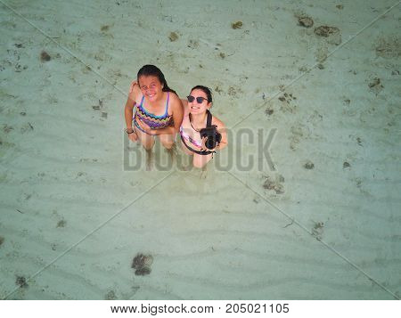 Two friends take pictures on beach aerial above view