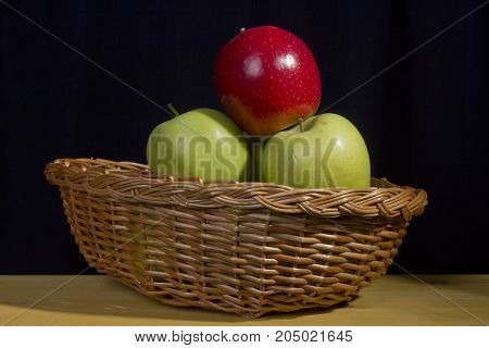 Multicolored apples in a wicker basket on a black background