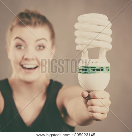 Happy woman holding eco modern light bulb. Innovation technology power saving concept.