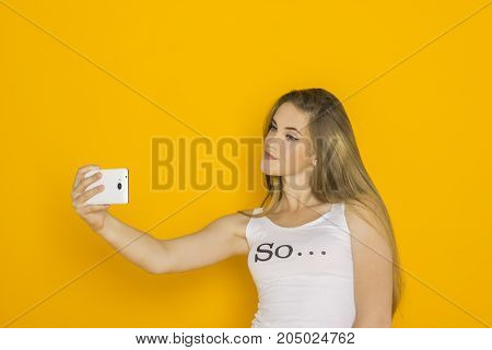 Young attractive woman make selfie on her smartphone. Fashion girl with mobile phone reads message. Studio shot orange background
