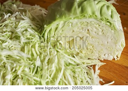pieces of chopped cabbage and part of the head are on wooden surface