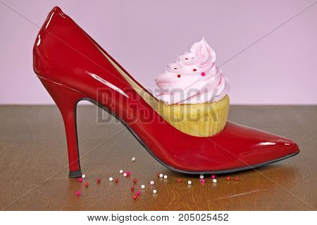 cupcake with pink frosting in red high heel shoe on wood