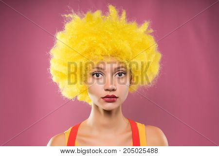 Sad girl clown in yellow wig on pink background