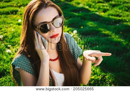 Woman with smartphone pointing to. Girl in sunglasses,summer