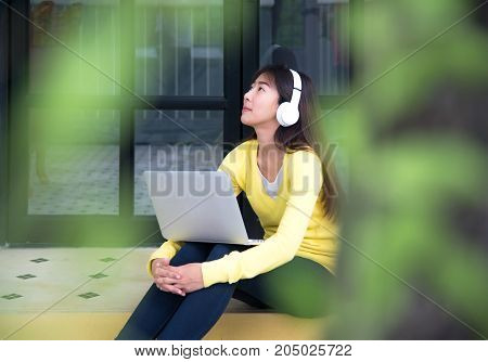 Lifestyle Girl enjoy listening music and play laptop in the nature park. Music and Lifestyle Concept.