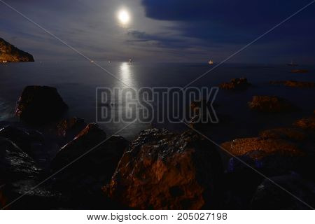 Moon over blue water at night sky