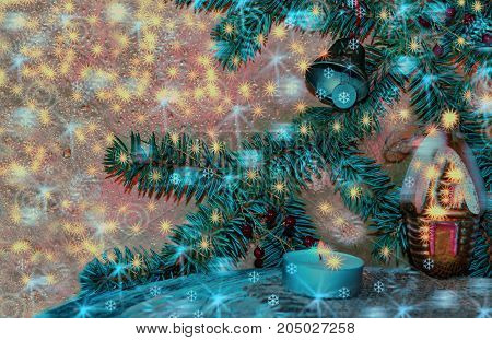 Christmas and new year background. Branch of green fir with a toy house on wooden surface with a candle on the background lights blur