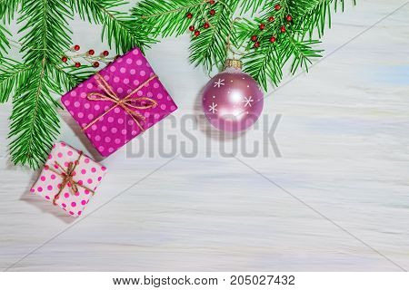 Christmas and new year background. Branch of green fir pre-packaged gift boxes and Christmas ball on a light colored wooden table