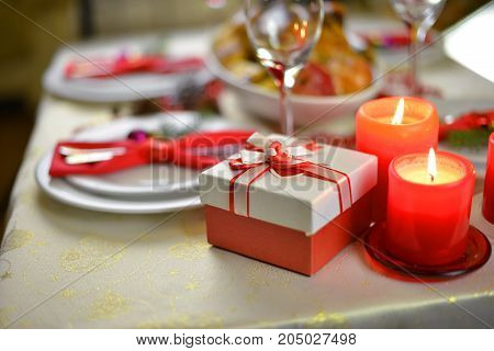 table setting with candles. fork knife and red napkin on dish