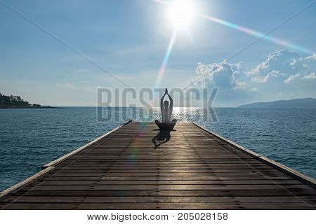 Healthy woman lifestyle exercising vital meditate and practicing yoga at on the bridge seashore nature background. Healthy Concept.