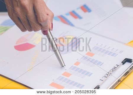 Business woman holding pen and point on graph in workplacebusiness concept