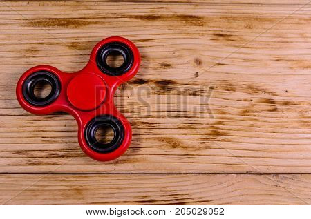 Red Fidget Spinner On Wooden Desk. Top View