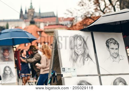 Prague, Czech Republic - September 27, 2014: Street portrait painter and examples of his art drawn with pencil in balck and white.