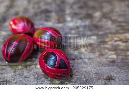 Four Whole Nutmeg Red Placenta-like Cover Of Seed On Wooden Background.