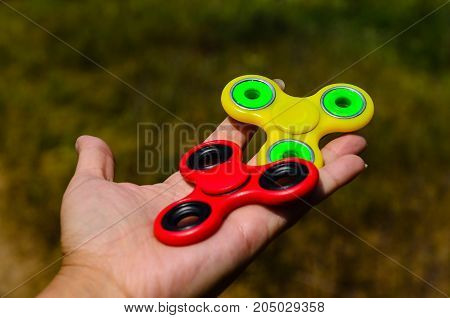 Red And Yellow Fidget Spinners In Female Hand