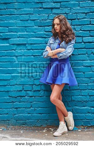 Beautiful Young Woman In White Sneakers On A Blue Brick Wall Background