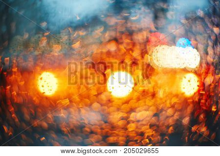 Headlights through glass with rain drops. Blur bokeh defocused background