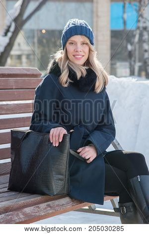 Beautiful young woman on a bench a sunny winter day with a black big bag