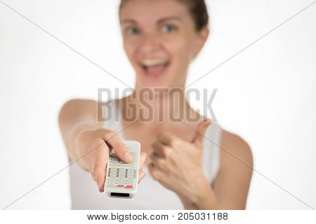 Young beautiful girl with remote control pressing on buttons smiling and showing okay sign on white background