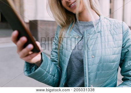 Telecommunications in real life. Girl with gadget, modern communication, young blonde with mobile phone on street