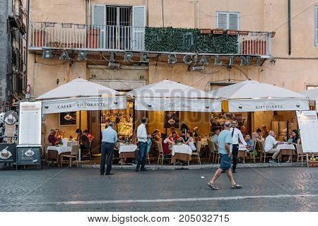 Rome, Italy - August 20, 2016: Sidewalk restaurant with tourists in Navona square in Rome a sunny summer day.