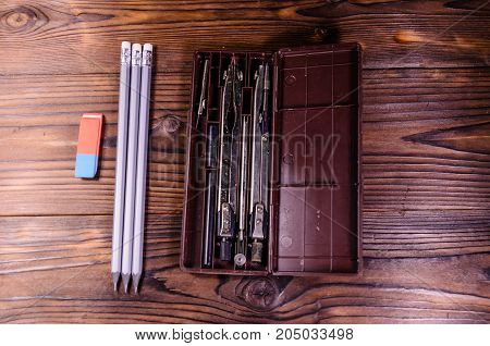 Case Of Drawing Instruments, Pencils And Eraser On Wooden Table. Top View