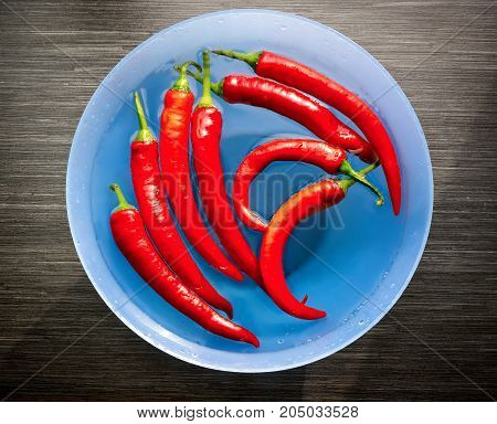 Red cayenne peppers (Capsicum annuum) in bowl on wooden table. Top view. Also known as Guinea spice, cow-horn pepper, red hot chili pepper, aleva, bird pepper.