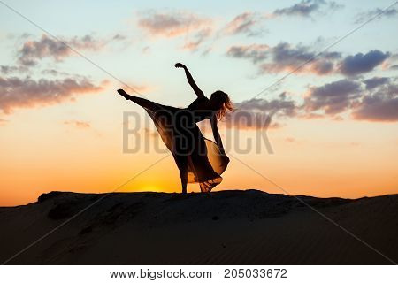 Woman dances at sunrise in the sun. The backlight of the sun only contours of the figures are visible.