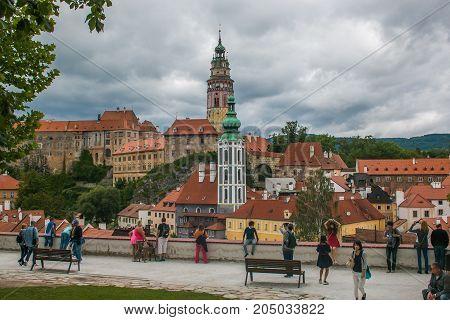 CESKY KRUMLOV, CZECH REPUBLIC - AUGUST 13, 2017: Tourists admiring the panorama of Cesky Krumlov city and the castle