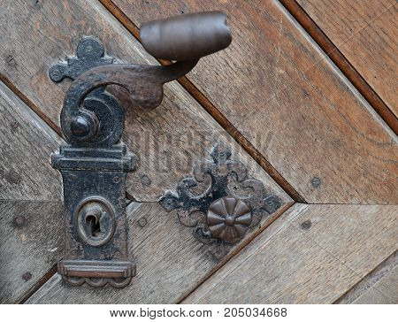 Vintage rusty door handle on wooden door