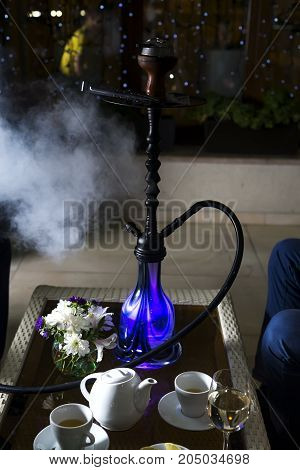 Hookah hot coals on shisha bowl on a cafe background. Stylish oriental shisha. Holiday Concept