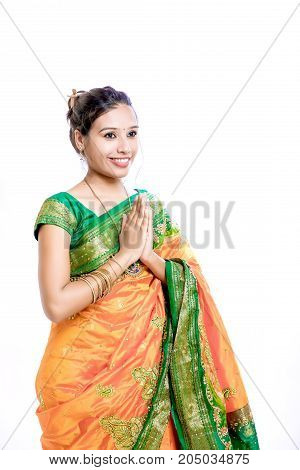 Happy young beautiful traditional Indian woman in traditional saree, Welcome Posing