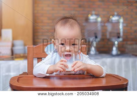 Portrait of Cute little Asian 18 months / 1 year old baby boy child drinking milk in a glass Toddler sitting in high chair at restaurant (cafe hotel) holding glass of milk at breakfast time