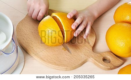 The child cutting a knife orange closeup