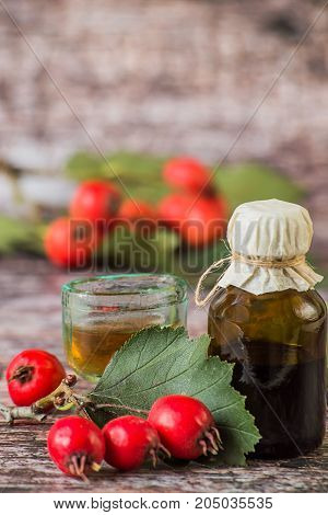 Tincture of hawthorn in a small glass bottle and fresh hawthorn fruit with leaves on a wooden background. Used in folk and traditional medicine.