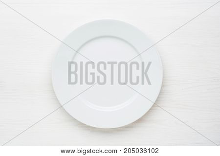 Empty plate on white wooden background. Top view with copy space.