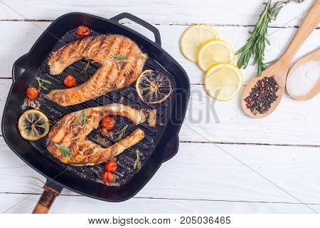 Grilled salmon steak with tomato lemon and rosemary . Top view space for text