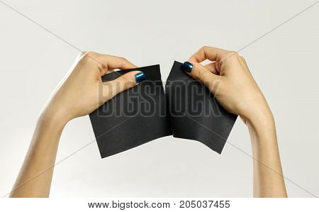 Female Hands Rip A Black Sheet Of Paper. Isolated On Gray Background. Closeup