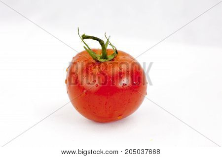 Juicy tomato on the white background with green leaf and droops with copy space