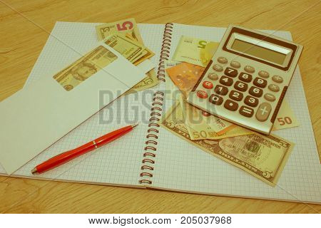 analysis of the annual budget with calculator and money on the table. financial concept. Business Objects in the office on the table - Retro color