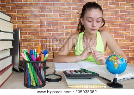 Young girl sitting at a table and reading a book. Education and school concept