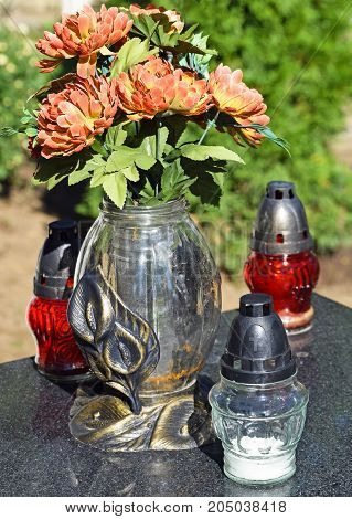 Lanterns and flowers on the tombstone in the public cemetery