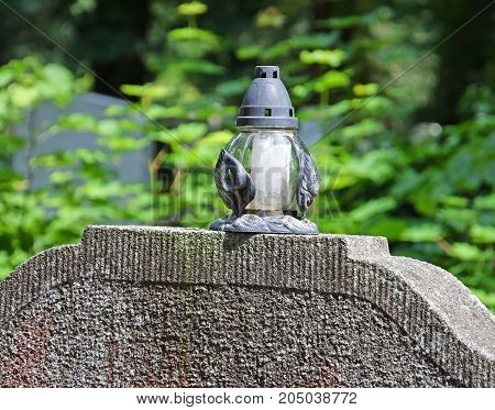 Lantern on the Tombstones in the Public cemetery in summer