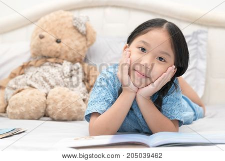 Cute Little Asian Girl Reading Fairy Tales On Bed