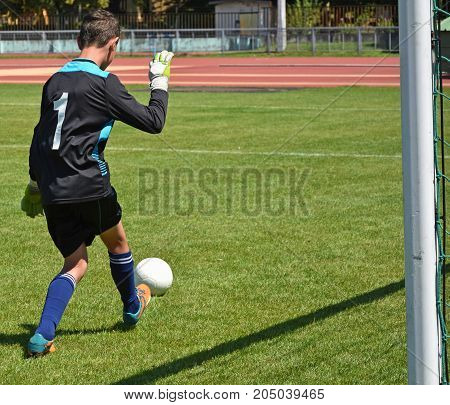 Young goalkeeper with a ball at the match