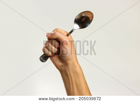 Male Hands Holding A Metal Tablespoon. Isolated On Gray Background. Closeup