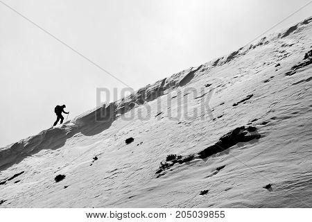 Small figure of skier, climbing a mountain