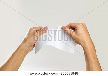 Male Hands Rip A White Sheet Of Paper. Isolated On Gray Background. Closeup