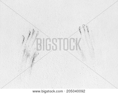 imprint of human hands on a white wall
